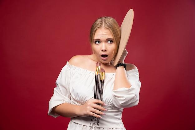 Художник-блондинка держит палитру и кисти и выглядит удивленным и сбитым с толку.
