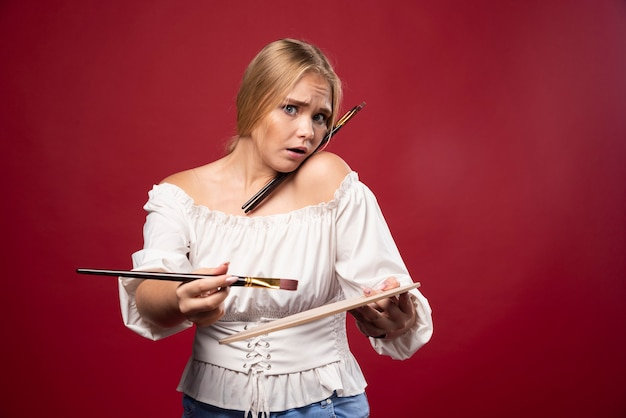 Blonde artist holds a palette and brushes and looks surprized and confused.