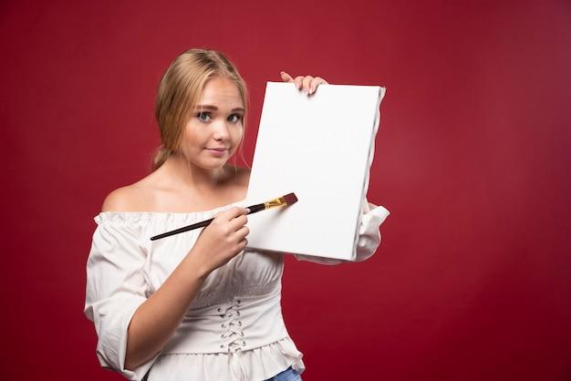 Artista bionda che mostra la sua opera d'arte e sembra dubbiosa.