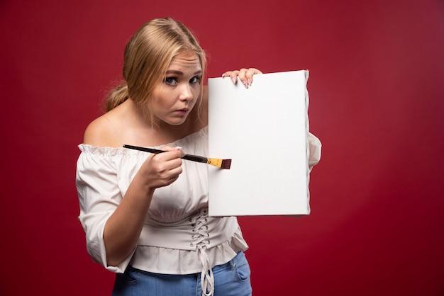 Художница-блондинка с нерешительностью показывает свои работы и ищет отзывы.