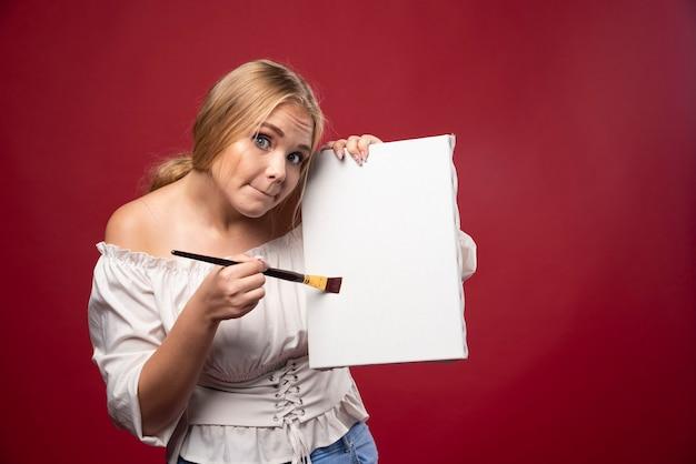 Artista bionda che mostra la sua opera d'arte con esitazione e cerca recensioni.