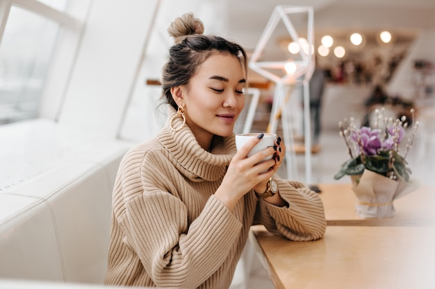 Blonde asian woman in oversized sweater holding white cup of tea