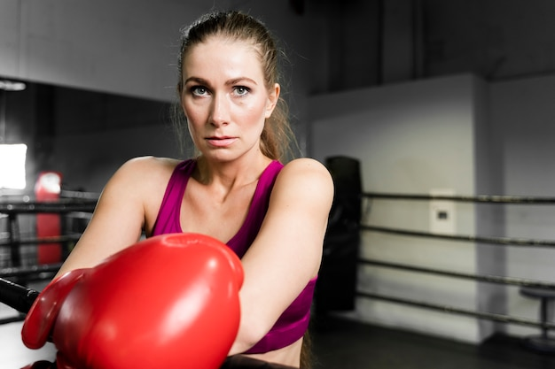 Blonde athletic woman in boxing training center