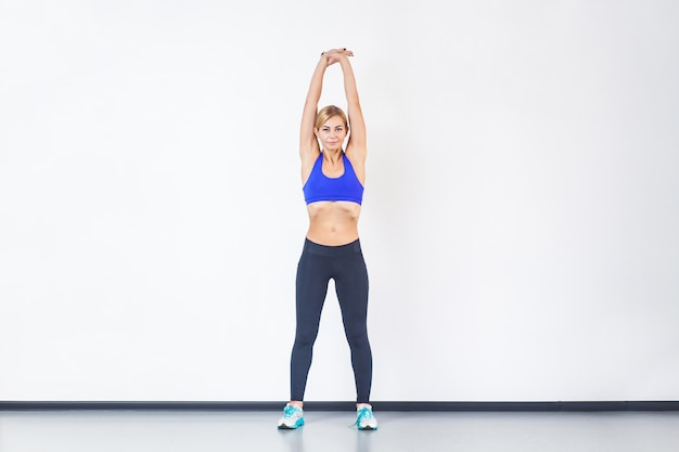 Blonde athletic woman hands up, doing fitness exercise. studio shot