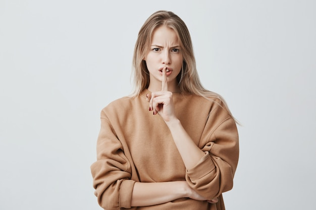 Blonde attractive european female keeps finger on lips, being displeased and asks not to make noise