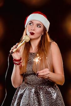 ステージ上のマイクと線香花火と赤いセーターと赤いサンタ帽子の金髪の魅力的な女性