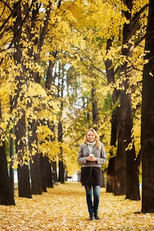 Blonde attractive woman walking at the nature in autumn time good active day concept