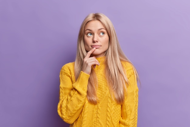 Blonde attractive young european woman keeps finger on lips looks with pensive expression above makes important decision builds plans in mind wears yellow sweater