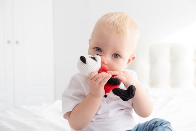 ベッドの上でかぎ針編みのおもちゃで遊ぶ金髪の男の子。