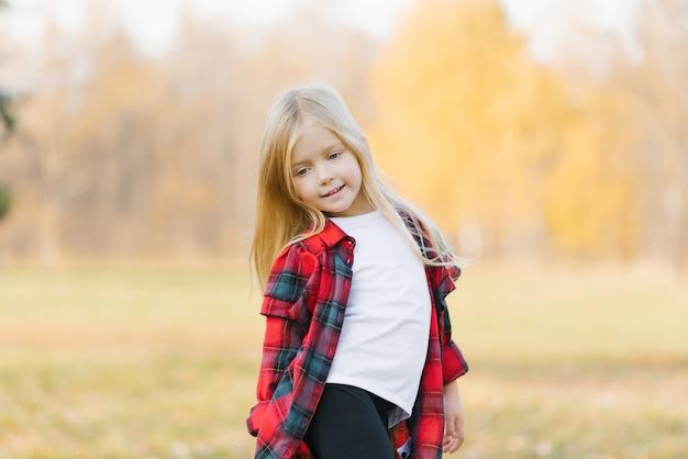 Блондинка девочка мечтает в осеннем парке. прогулка днем