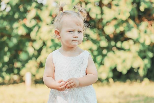 Блондинка девочка в парке летом. фото высокого качества