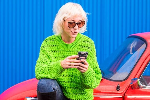 金髪の美しい中毒の女の子は、赤いビンテージ クラシックカーに座って屋外で携帯電話を使用します。