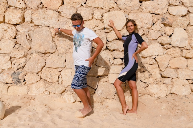 A blonde, a beautiful girl in a wetsuit and a guy are posing on a sunny day, on the shore against the background of a stone wall.