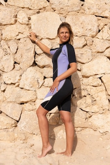 A blonde, beautiful, girl in a wetsuit posing on a sunny day, on the shore against the background of a stone wall.