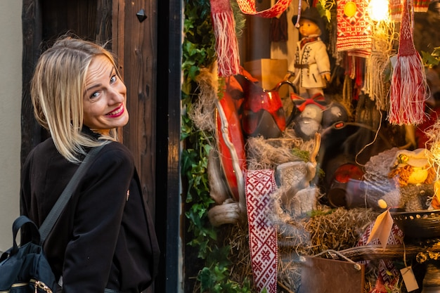夜の光の通りの店の窓で金髪、美しい女性