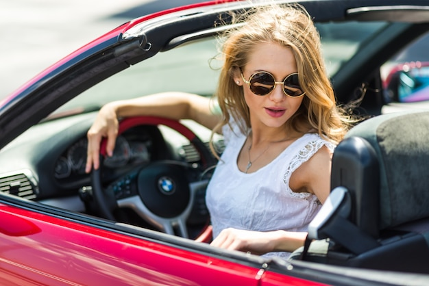 Blonde beautiful woman in sunglasses sitting in red car by the sea. sea view. vacation concept. happyness. freedom. road trip on beautiful sunny summer day