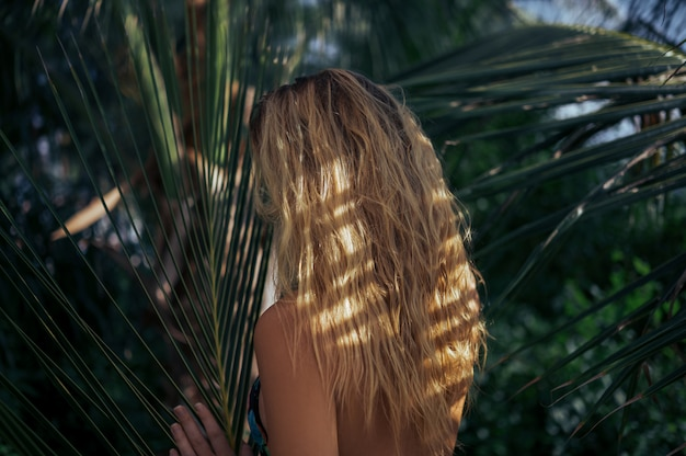 Blonde beautiful woman with wet hair posing in jungle tropical park back view. travel adventure nature in china, tourist beautiful destination asia, summer holiday vacation journey trip concept