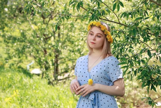 밝은 파란색 드레스와 여름 정원에서 민들레 화환에 금발의 아름다운 젊은 여자