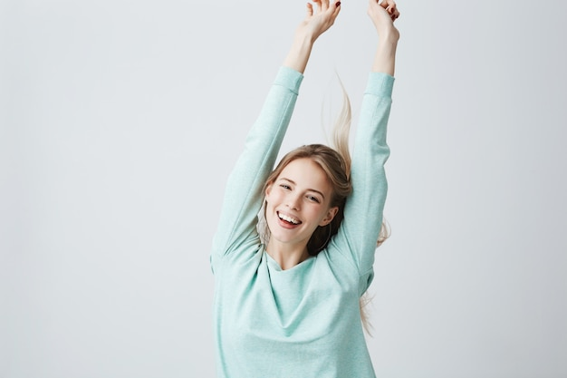 Blonde beautiful young woman in light blue top stretching arms up in cheerful mood like celebrating victory. broadly smiling female showing white teeth and positive emotions, having fun indoors.