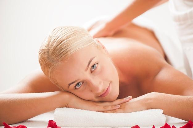Блондинка красивая молодая женщина получает массаж