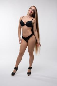 Блондинка-красотка позирует в сексуальном черном белье