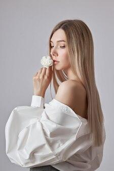 금발의 미인은 흰 꽃을 손에 들고 있다. 아름다운 부드러운 손과 부드러운 피부. 뷰티 핸드 케어용 화장품