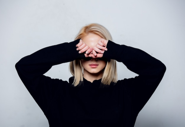 Blonde in black hoodie hides a face on a white background