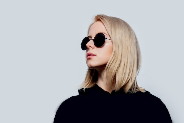 Blonde in black and round sunglasses on a white background