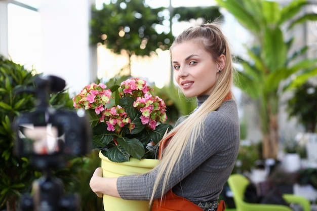 Blonde blogger holding flowerpot with hydrangea