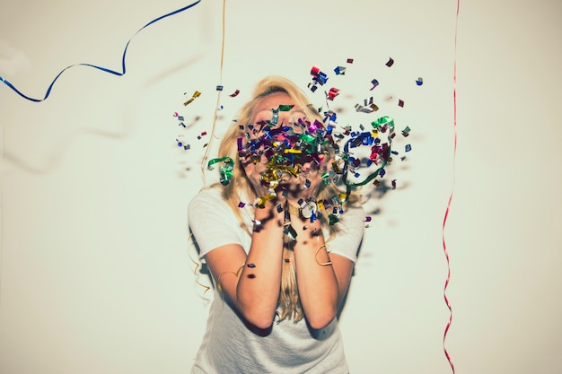 Blonde blowing confetti and hiding her face