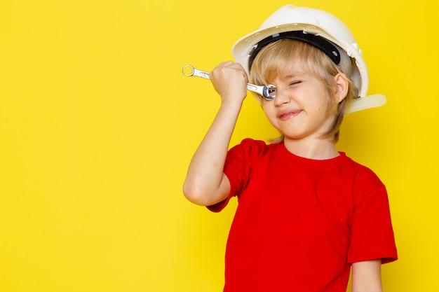 Белокурый милый мальчик в красной футболке и белом шлеме на желтой стене