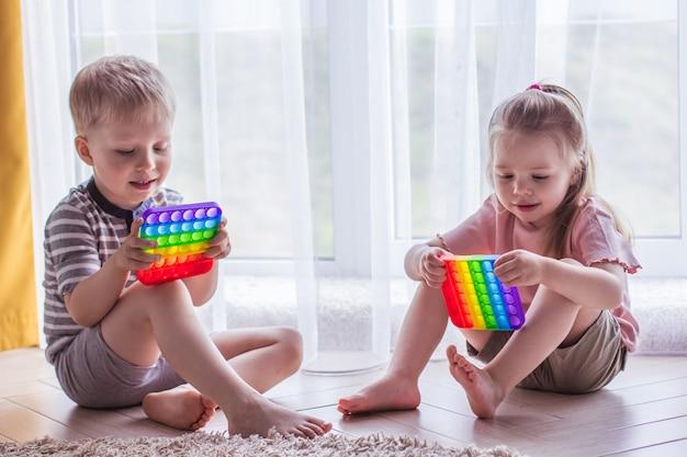 금발 소년과 소녀 아이들은 감각 장난감을 팝니다. 스트레스를 받는 어린이와 성인을 위한 트렌디한 실리콘 손놀림 게임. 뽀송뽀송한 거품 장난감. 무지개색 팝잇을 가지고 노는 아이