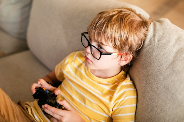 Blonde boy in big glasses playing on the console sitting on the couch. european child having a hobby