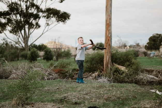 自然の中で薪のために木の枝を2つの部分に分割するブロンドの少年
