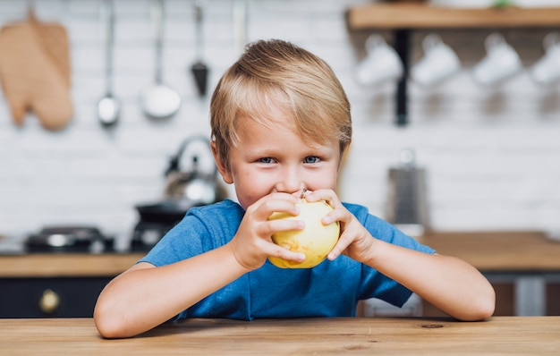 Blonde boy eating an apple