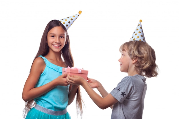 Blonde boy in festive paper hat gives present in gift box to happy girl on her birthday party
