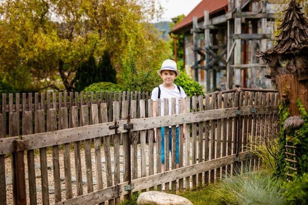 Blonde boy in the hat and big glasses near the old wooden fence in the country