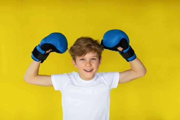 Белокурый мальчик в синих боксерских перчатках и белой футболке на желтом фоне