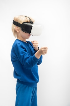 Блондинка мальчик в очках виртуальной реальности 3d. изолированный на белой поверхности. вертикальная рамка.