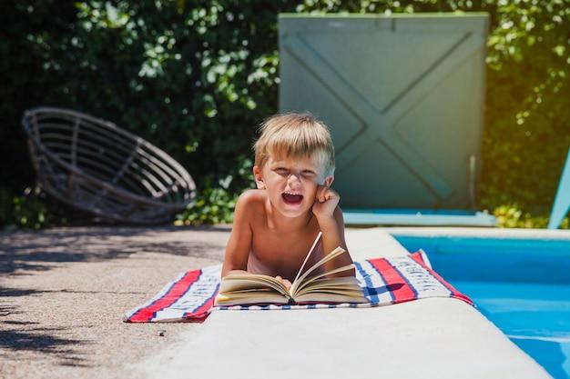 Blonde boy lying on towel by pool