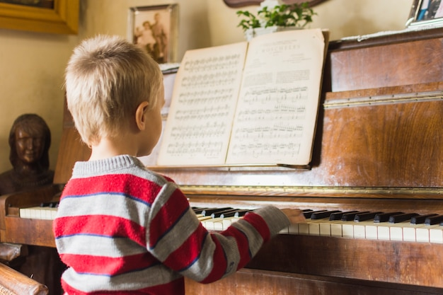 Blonde boy playing piano at home