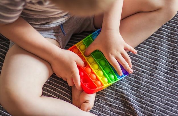 Блондинка мальчик играет с радугой, хлопай игрушку-непоседу. сенсорная игрушка push bubble fidget - моющаяся и многоразовая игрушка для снятия стресса. антистрессовая игрушка для ребенка с особыми потребностями. концепция психического здоровья