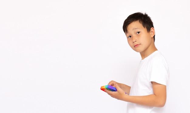 레인보우를 가지고 노는 금발 소년은 장난감을 팝니다. 푸시 버블 피젯 감각 장난감 - 빨고 재사용할 수 있는 스트레스 해소 장난감. 특별한 도움이 필요한 어린이를 위한 스트레스 방지 장난감. 정신 건강 개념