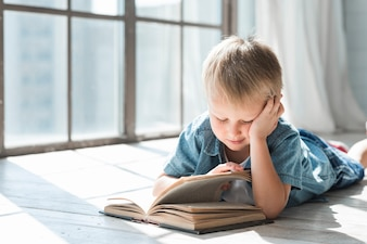 Blonde boy reading book near the window in the sunlight