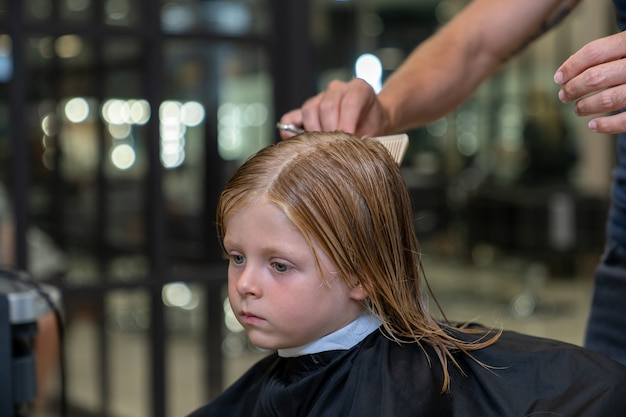 A blonde boy sits in a chair in a hairdresser and a stylist combs his hair before cutting