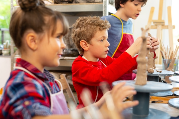 クラスメートの近くに座って粘土動物をモデリングする金髪の少年