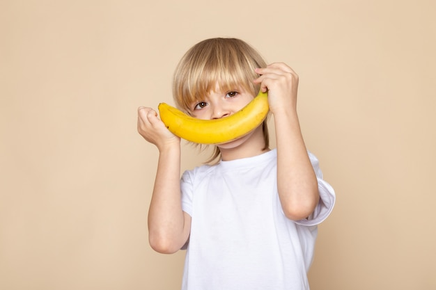 Белокурый мальчик, улыбающийся милый сладкий с бананом в белой футболке на розовом столе