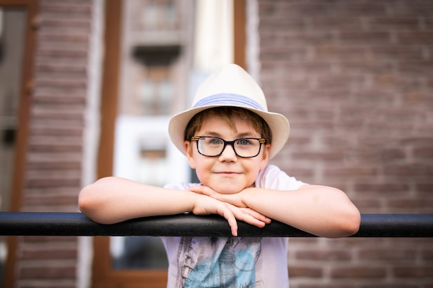Blonde boy in the straw hat and big glasses staying among beautiful old houses