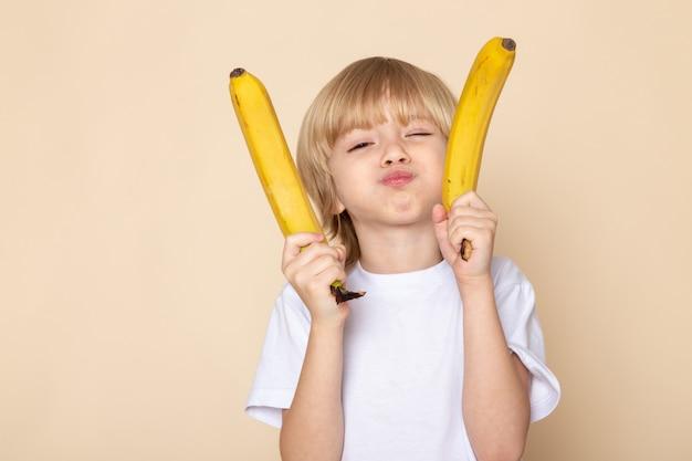 Белокурый мальчик с бананами в белой футболке на розовой стене