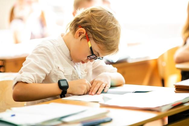 大きな黒い眼鏡をかけた金髪の少年が教室に座って、勉強して、笑っています。小学校での教育、学校での初日。